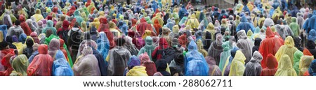 Crowd in colorful plastic raincoat ponchos - stock photo