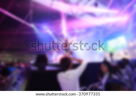 Crowd in front of concert stage with dancer blurred