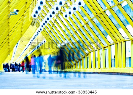 Crowd in motion in yellow corridor - stock photo