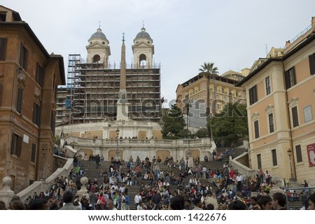 Crowd in Square di Spagna, Rome where people take rest . at left the house of famous English poet Keats, obelisk on the middle. Beyond scaffolds, the French church of Saint Trinity.
