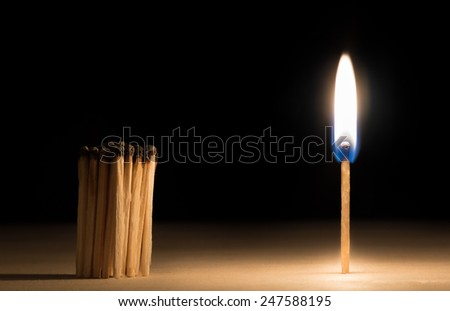 Crowd of burnt  matches standing before match on fire concept of motivation leadership on black - stock photo