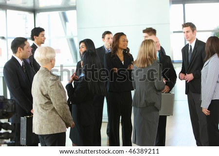 Crowd of businesspeople in lobby - stock photo