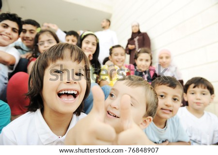 Crowd of children, different ages and races in front of the school, breaktime - stock photo