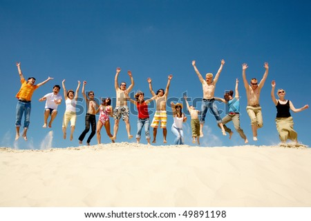 Crowd of friends jumping on sandy beach with their arms raised against blue sky - stock photo