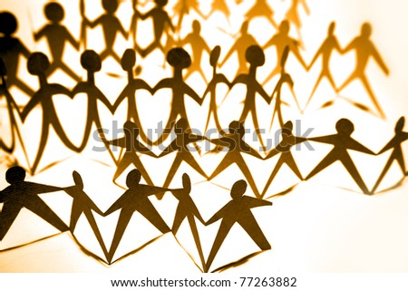 Crowd of paper doll people holding hands - stock photo