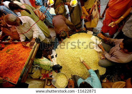 Crowd of people around flowers for sale in market in Mysore, India - stock photo