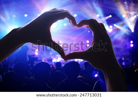 Crowd of people at during a concert with a heart shaped hands shadow - stock photo