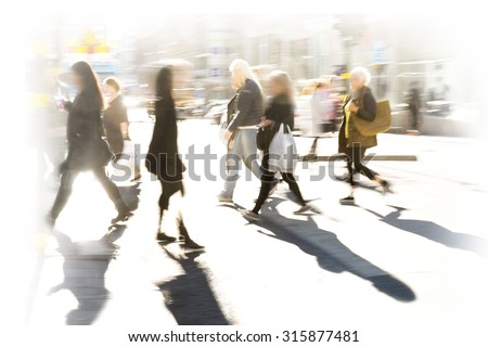 Crowd of people in blurred motion on pedestrian crossing at rush hour in bright sunshine - stock photo