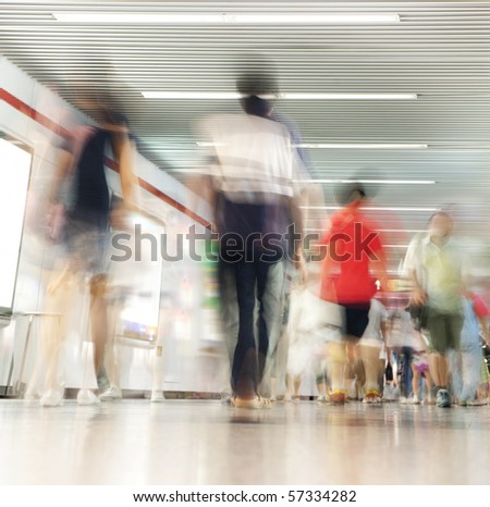 Crowd of people in corridor in subway, blurred motion - stock photo