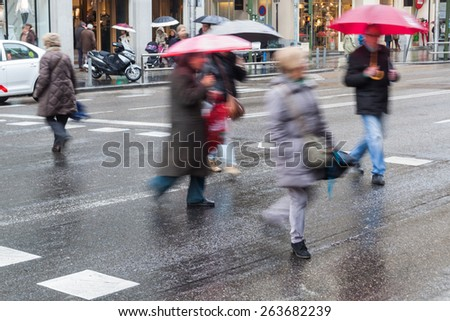 crowd of people in motion blur crossing a rainy city street