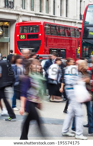 crowd of people in motion blur crossing the Oxford Circus in London - stock photo