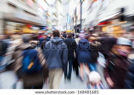 crowd of people in the shopping street of a city with intentional zoom effect - stock photo