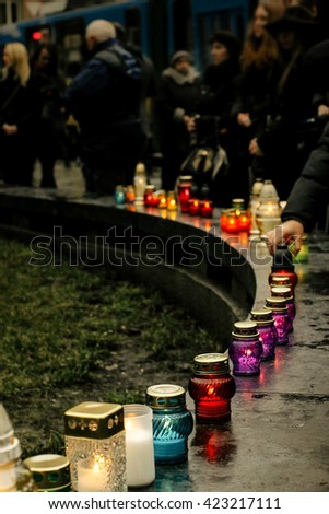 crowd of people lighting candles in city center, mourning victims in terrorism attacks and revolutions, sadness moment - stock photo