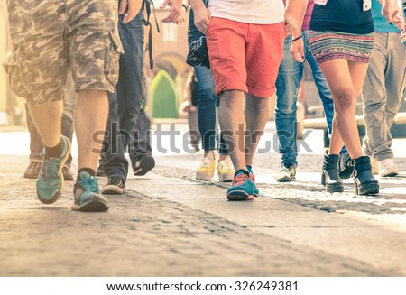 Crowd of people walking on the street - Detail of legs and shoes moving on sidewalk in city center - Travelers with multicolor clothes on vintage filter - Shallow depth of field with sunflare halo - stock photo