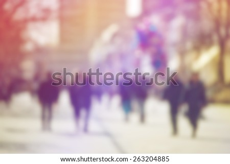 Crowd of People Walking On the Street in Bokeh, unrecognizable group of men and women as blur urban background - stock photo