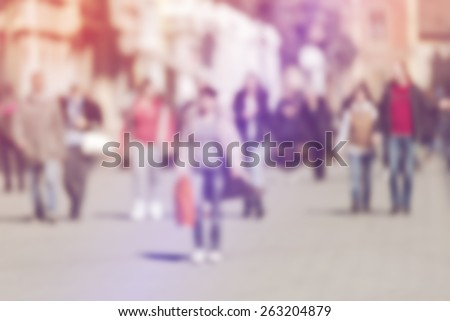 Crowd of People Walking On the Street in Bokeh, unrecognizable group of men and women with shopping bags as blur urban background - stock photo