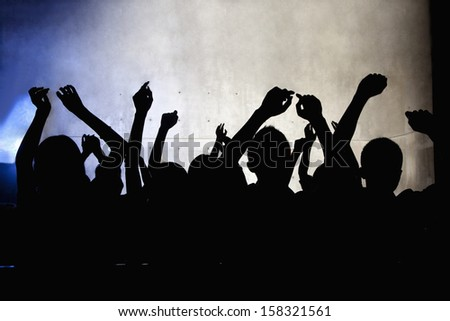 Crowd of young people dancing in nightclub - stock photo