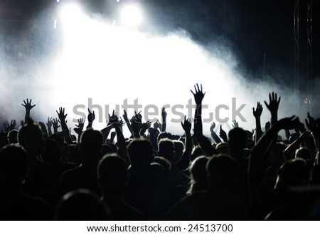 Crowd raising hands at a pop concert;  white and grey-blue fog - stock photo