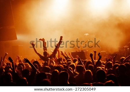 Crowd surfing during a musical performance - stock photo