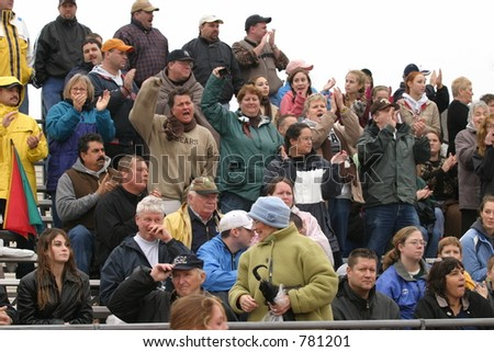 Crowd watching and cheering at a sporting event. Editorial use only.