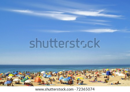 Crowded Atlantic summer beach in Carcavelos, Portugal - stock photo