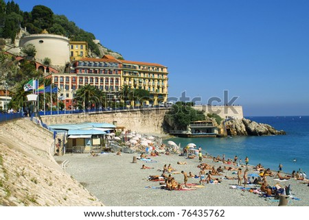 Crowded Mediterranean summer beach in City of Nice, France - stock photo