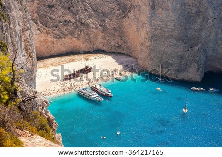 Crowded Navagio Beach on Zakynthos seen from the cliff - stock photo