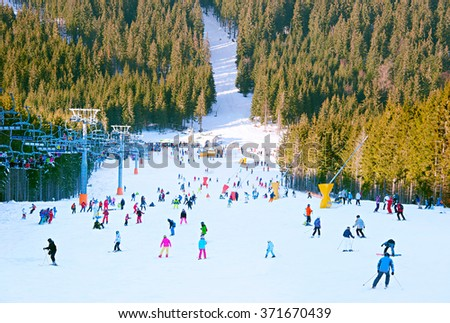 Crowded ski slope in the mountains at ski resort - stock photo