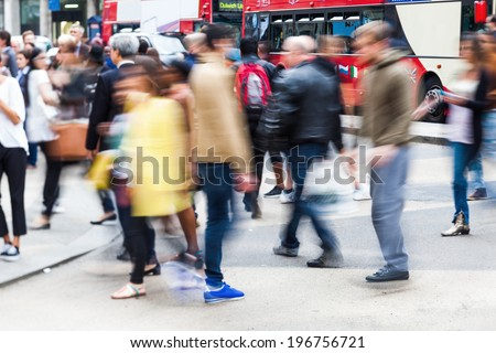 crowds of busy people crossing the street in the city of London