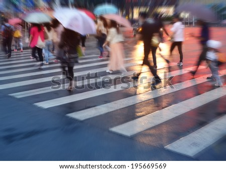 crowds of people crossing the street on a rainy day in the city  - stock photo