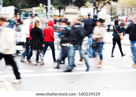 crowds of people in motion blur crossing the street - stock photo