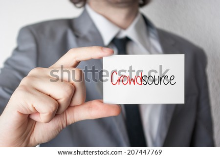 Crowdsource. Businessman in suit with a black tie showing or holding business card - stock photo