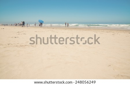 Crowdy sunny beach with blue umbrella and clear sky. Morgans Bay. Eastern Cape. South Africa. - stock photo