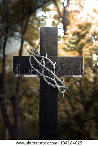 Crown and thorns hanging on easter cross - stock photo