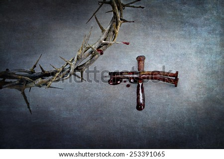 Crown of thorns and cross of nails with blood puddled on ends. - stock photo