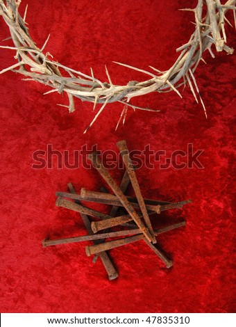 Crown of Thorns and rusty metal spikes on a rich red background. - stock photo