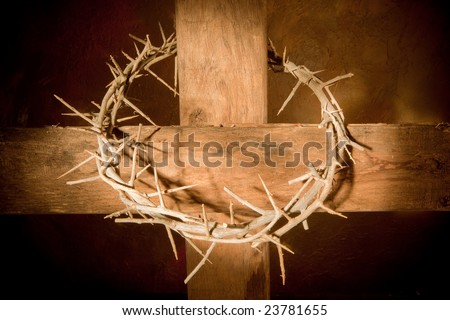 Crown of thorns hanging on a wooden cross at Easter - stock photo