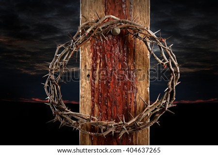 Crown of thorns over cross held by nail - stock photo