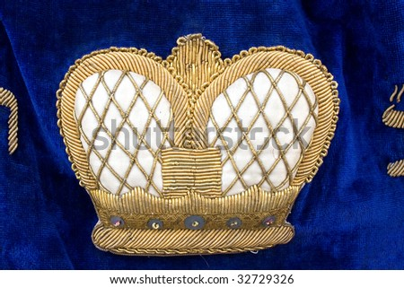 Crown on vintage colorful Torah Ark Curtain, Flea Market, Tel-Aviv. - stock photo