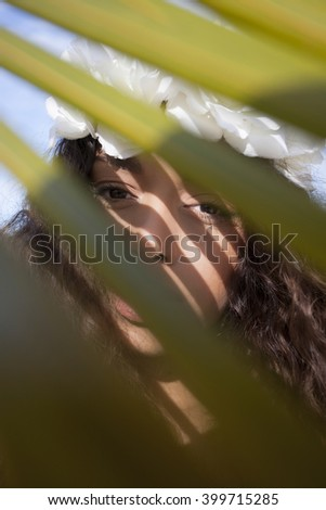 Crowned girl is behind the leaves on the beach. - stock photo