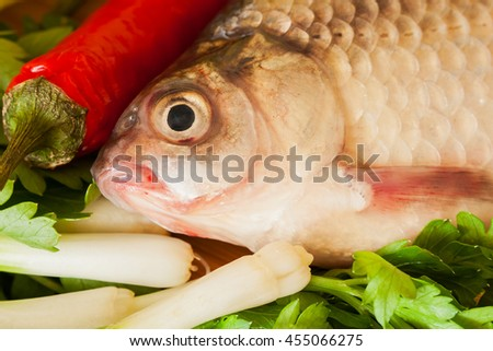 Crucian fish with green vegetables, red chili - stock photo