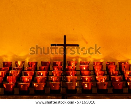 Crucifix and red candle holders with cross in Catholic church against old adobe wall - stock photo
