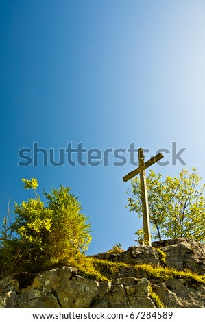Crucifix in the mountains against blue sky - stock photo