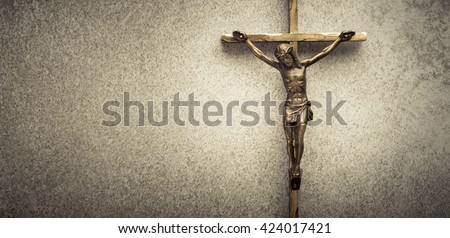 Crucifix of Jesus on the cross with stone background. Symbol of christian religion and belief. Image composed with copy space. - stock photo