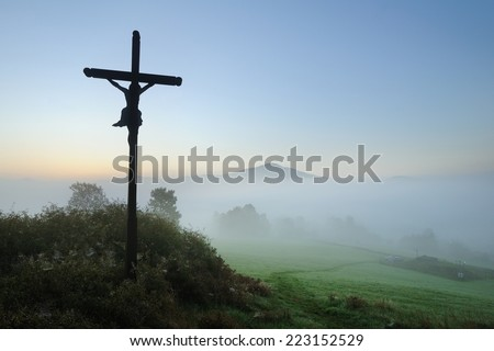 Crucifix on the holy and sacred hill with the beautiful view onto misty and foggy valley near national park Bohemian Switzerland - stock photo