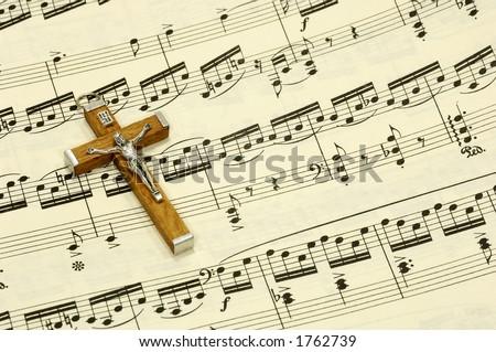 Crucifix on top of Sheet Music - stock photo