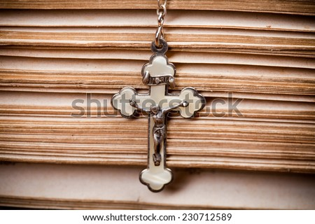 crucifix with jesus, hanging on sides of opened holy bible, closeup,  - stock photo
