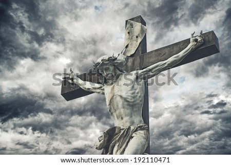 Crucifixion. Christian cross with Jesus Christ statue over stormy clouds. religion and spirituality concept. - stock photo