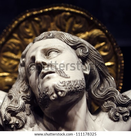 Crucifixion detail from 120 year old statue at Palma de Mallorca Cathedral in soft focus in background. - stock photo