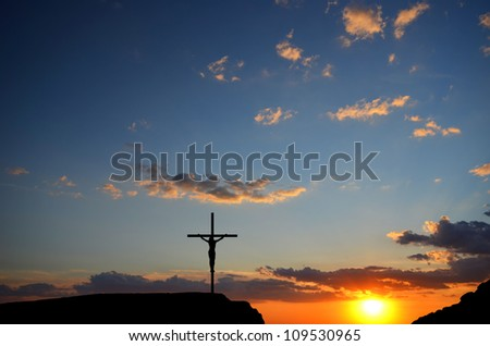 Crucifixion of Jesus Christ on the cross on a background sunset - stock photo